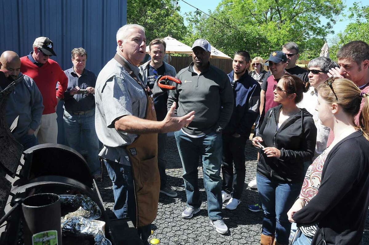 Mike Albrecht shows the class a sausage cooked on a smoker at a BrisketU class at Town in City Brewing Co.