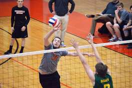 Edwardsville middle senior Will Bode, left, tips a ball past Metro-East Lutheran blocker A.J. Risavy during first-game action Wednesday inside Lucco-Jackson Gymnasium.