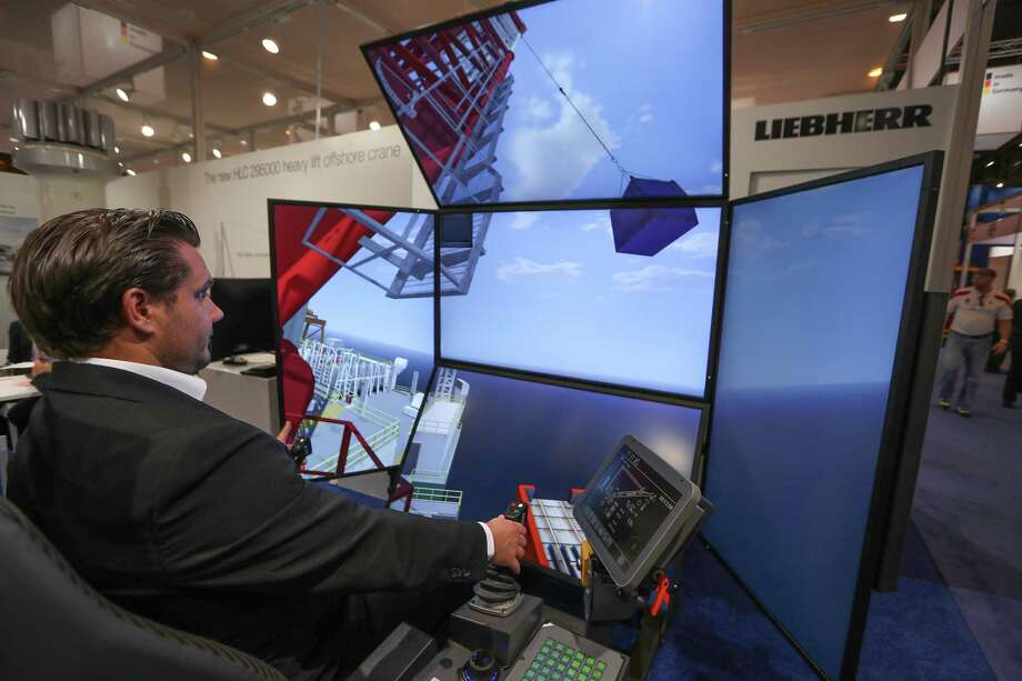 Alek Kolin, technical advisor Liebherr USA, Co., demonstrates a virtual reality crane at their Offshore Technology Conference (OTC 2017) booth Wednesday, May 3, 2017, in Houston. ( Steve Gonzales  / Houston Chronicle ) Photo: Steve Gonzales, Staff / © 2017 Houston Chronicle