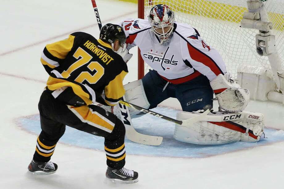 Pittsburgh's Patric Hornqvist, left, pushes the puck past Washington goaltender Braden Holtby in the first period of the Penguins' 3-2 win over the Capitals. Photo: Gene J. Puskar, STF / Copyright 2017 The Associated Press. All rights reserved.