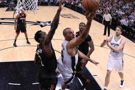 SAN ANTONIO, TX - MAY 03:  Tony Parker #9 of the San Antonio Spurs drives against Patrick Beverley #2 and Nene Hilario #42 of the Houston Rockets during Game Two of the NBA Western Conference Semi-Finals at AT&T Center on May 3, 2017 in San Antonio, Texas.  NOTE TO USER: User expressly acknowledges and agrees that, by downloading and or using this photograph, User is consenting to the terms and conditions of the Getty Images License Agreement.  (Photo by Ronald Martinez/Getty Images)