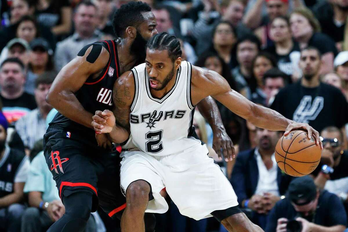 San Antonio Spurs forward Kawhi Leonard (2) looks to drive past Houston Rockets guard James Harden (13) during the first half of Game 2 of the second-round of the Western Conference NBA playoffs at AT&T Center, Wednesday, May 3, 2017, in San Antonio.