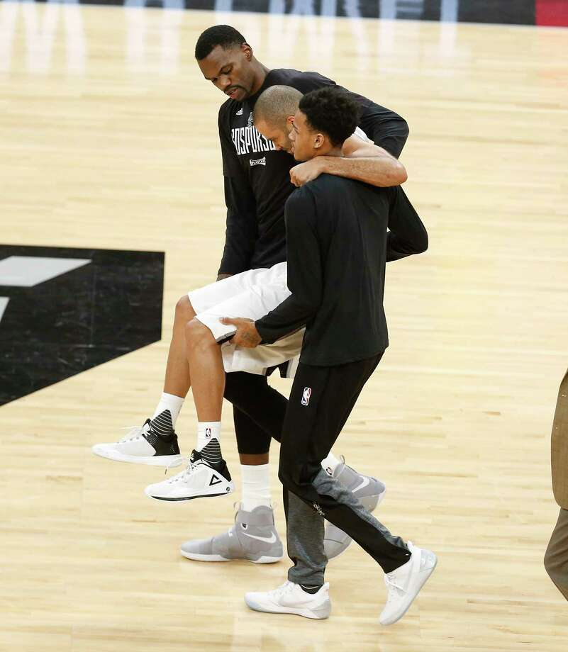 Spurs' Tony Parker gets carried off the court by teammates Dewayne Dedmon (03) and Dejounte Murray (05) after getting injured after a play against the Houston Rockets in the second half of Game 2 of the Western Conference semifinals at the AT&T Center on Wednesday, May 3, 2017. Photo: Kin Man Hui, San Antonio Express-News / ©2017 San Antonio Express-News