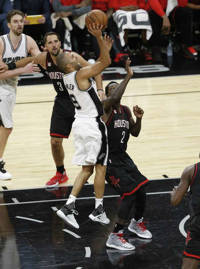 Spurs' Tony Parker, grimacing in pain, attempts a shot against Houston Rockets' Patrick Beverley in Game 2 at the AT&T Center on May 3, 2017. Parker was injured on this play and had to be carried off the court. Photo: Kin Man Hui /San Antonio Express-News / ©2017 San Antonio Express-News
