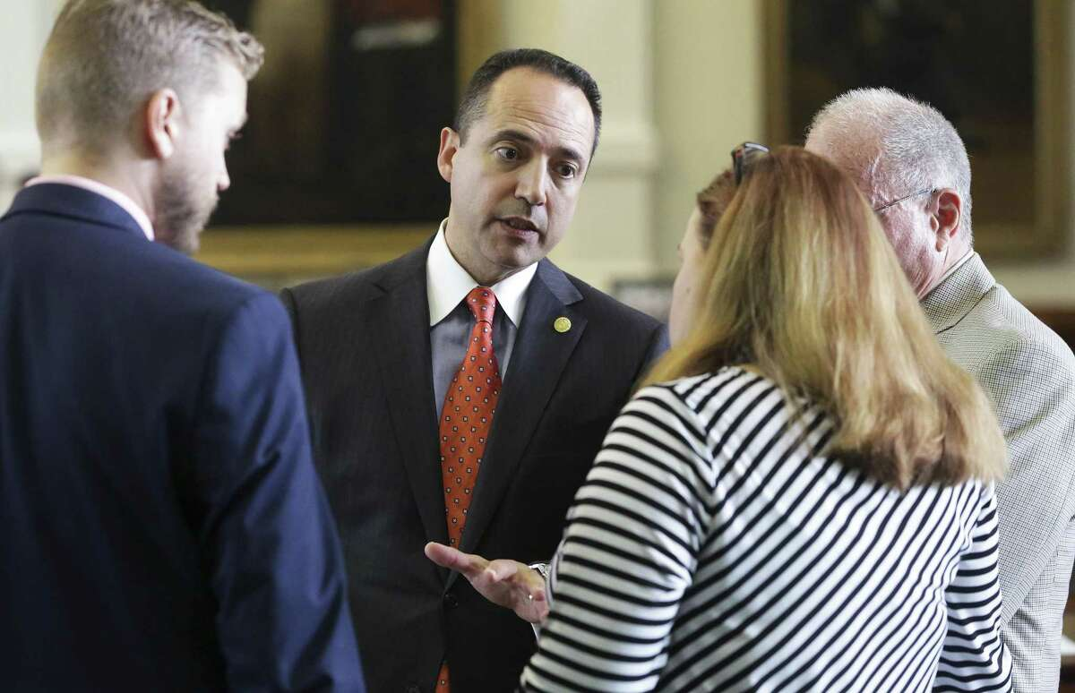 Senator Jose Menendez chats with his staff as he introduces bullying legislation on the floor of the Texas Senate on Wednesday, May 3, 2017.