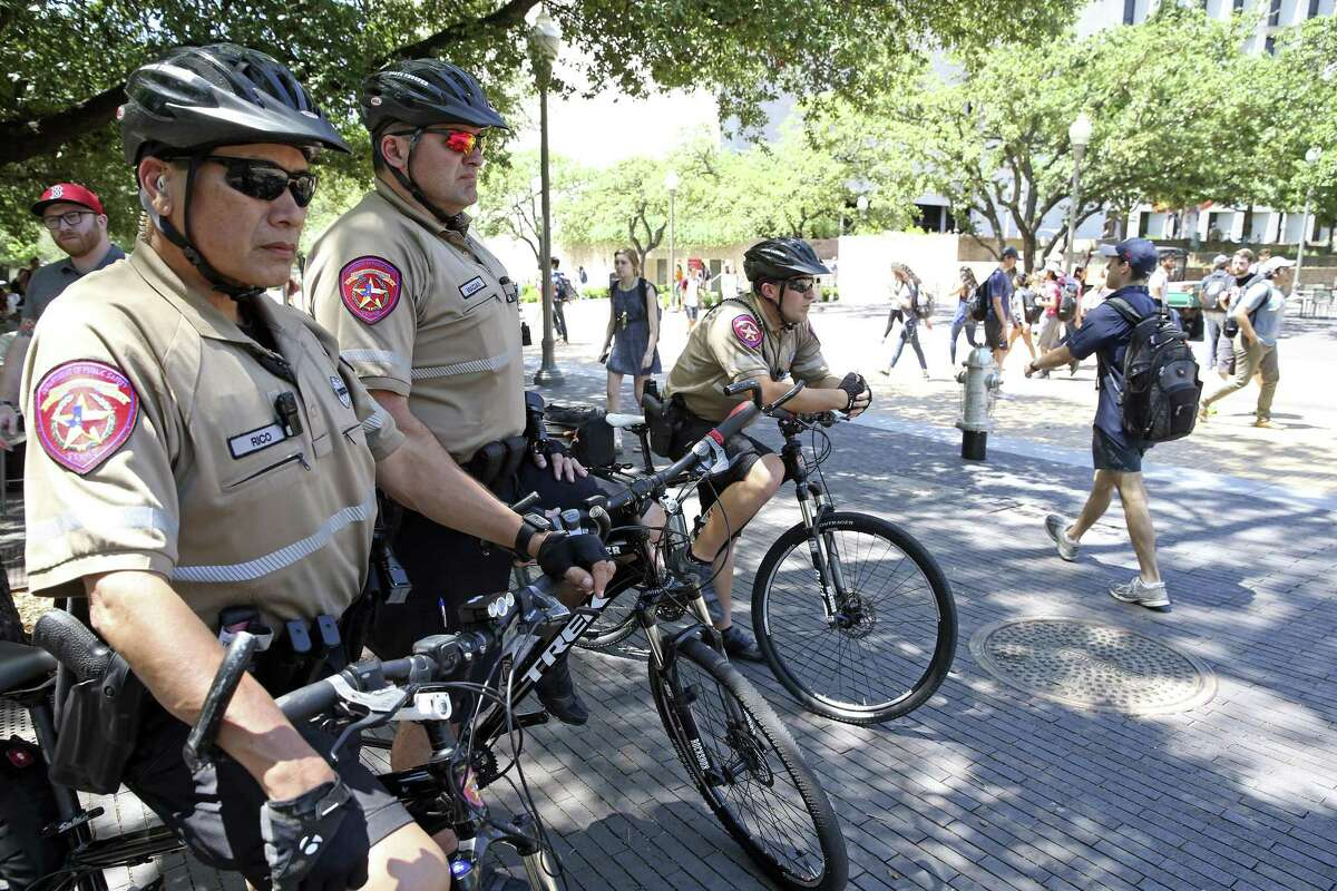 State Troopers (from left) Tony Ricco, Gabriel Macias and Guy Hoffman watch foot traffic on campus as extra police presence is noticeable on the University of Texas campus near Gregory Gym on Tuesday, May 2, 2017, one day after a wild stabbing spree took place at the scene.