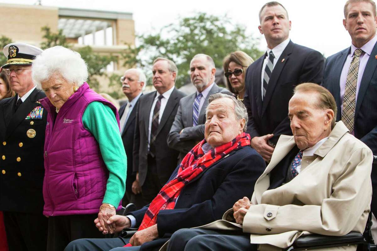 Former First Lady Barbara Bush, left, holds hands with her husband, former President George H.W. Bush and Sen. Bob Dole, R-Kansas, during the playing of Taps at the 75th anniversary ceremony of the attack on Pearl Harbor at the George Bush Presidential Library on Wednesday, Dec. 7, 2016, in College Station.