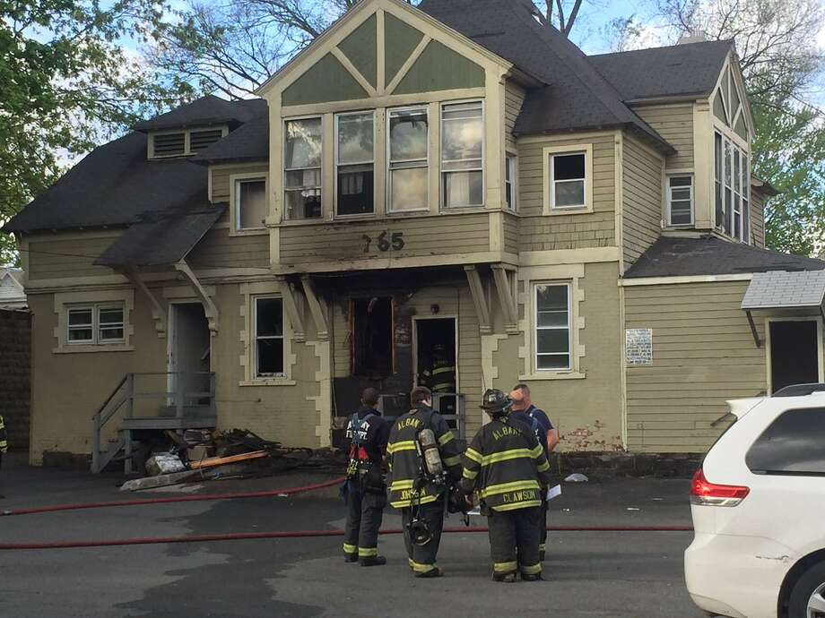 A woman was taken to the hospital after fire Wednesday damaged a home on Madison Avenue.  Photo: Robert Downen / Times Union