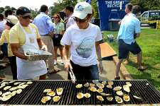 Marian Rossi grills oysters during the 40th Annual Milford Oyster Festival in downtown Milford, Conn. on Saturday, August 16, 2014.