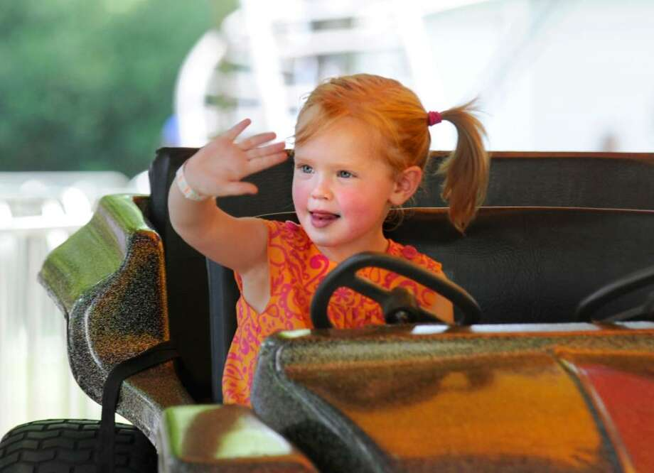 """Grace Butler, 3, of Riverside, waves to her mother Elizabeth Butler while on a car ride during St. Paul's Episcopal Church's annual """"Fair For All,"""" Riverside, Saturday, June 5, 2010. Photo: Bob Luckey / Greenwich Time"""