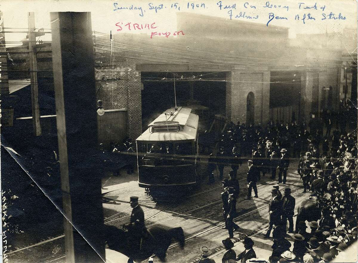 An image of police surrounding a car leaving the depot during the 1907 streetcar strike.
