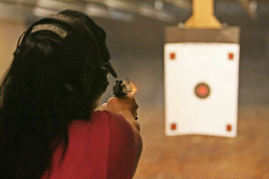 Showing proper form, Vicki Gonzalez, who joined The Well Armed Woman after her home was burglarized, fires a round at a target in 2015. Photo: John Goodspeed /For The Express-News / San Antonio Express-News