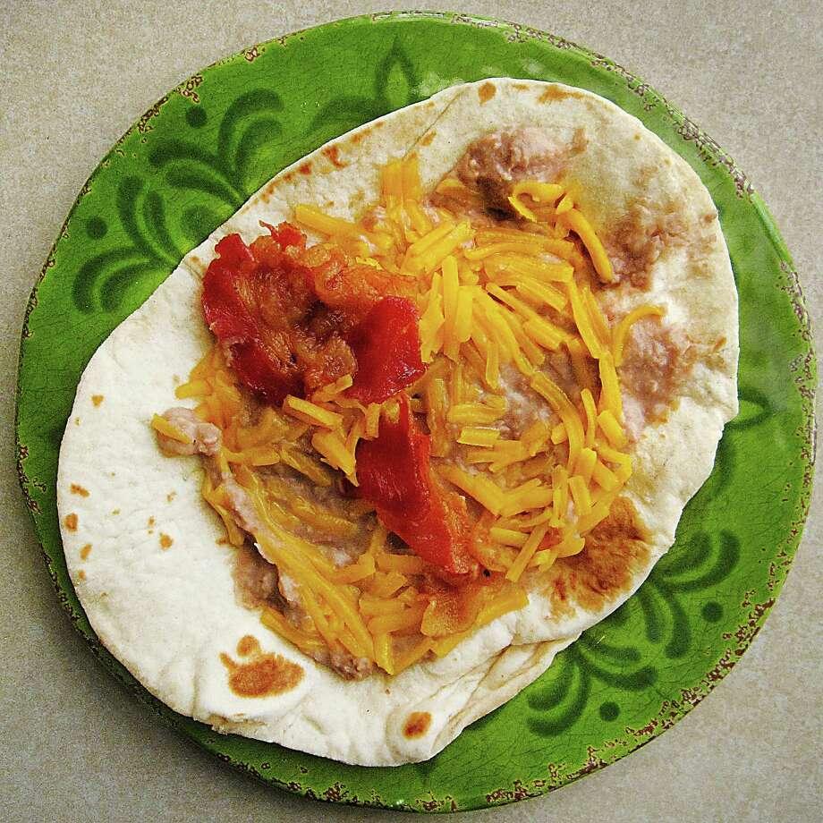 Bean and cheese with bacon taco on a handmade flour tortilla from La Parroquia Cocina Mexicana. Photo: Mike Sutter /San Antonio Express-News