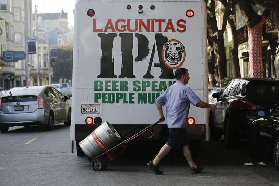Walking past a Lagunitas sign on his company truck, Jaime Siaenz with Matagrano Inc. beer distributing in So. San Francisco delivers a keg of beer (not Lagunitas) on Hayes Street in San Francisco, Calif. on Wednesday January 14, 2015