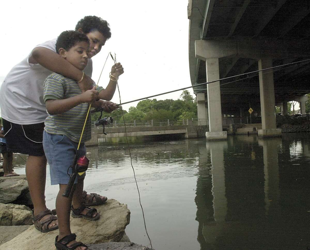 Greenwich, Aug..26 2002. Michael Arce, 13, helps his cousin, Chad Rodan, 4, with his fishing line. The children and their family and friends were fishing for snappers at the Mianus River, underneath the I-95 bridge. They are from Stamford. Photo/Helen Neafsey color.