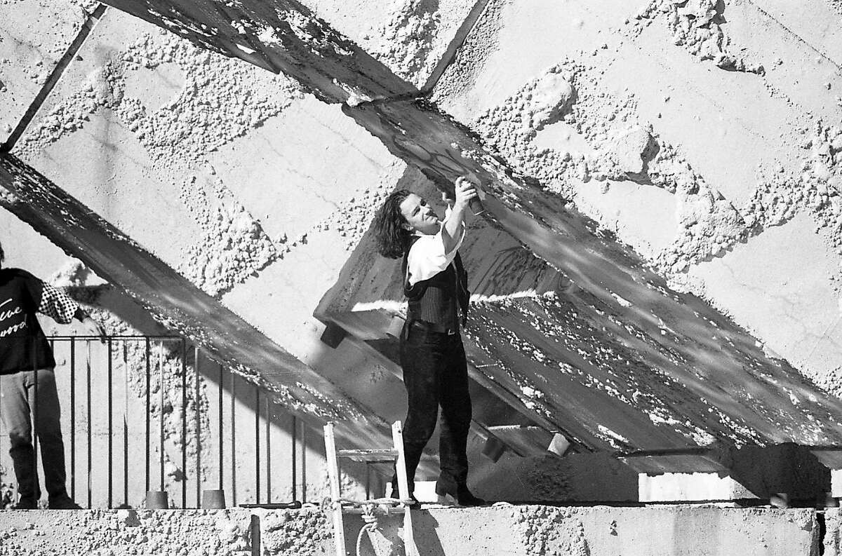U2 singer Bono spray paints the Vaillancourt fountain during a free concert at Justin Herman Plaza in San Francisco on Nov. 11, 1987. The painting of the fountain was a controversy, and showed up in the U2 concert movie