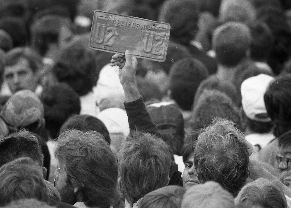 A fan holds up a U2 license plate at a free concert in Justin Herman Plaza San Francisco on Nov. 11, 1987.