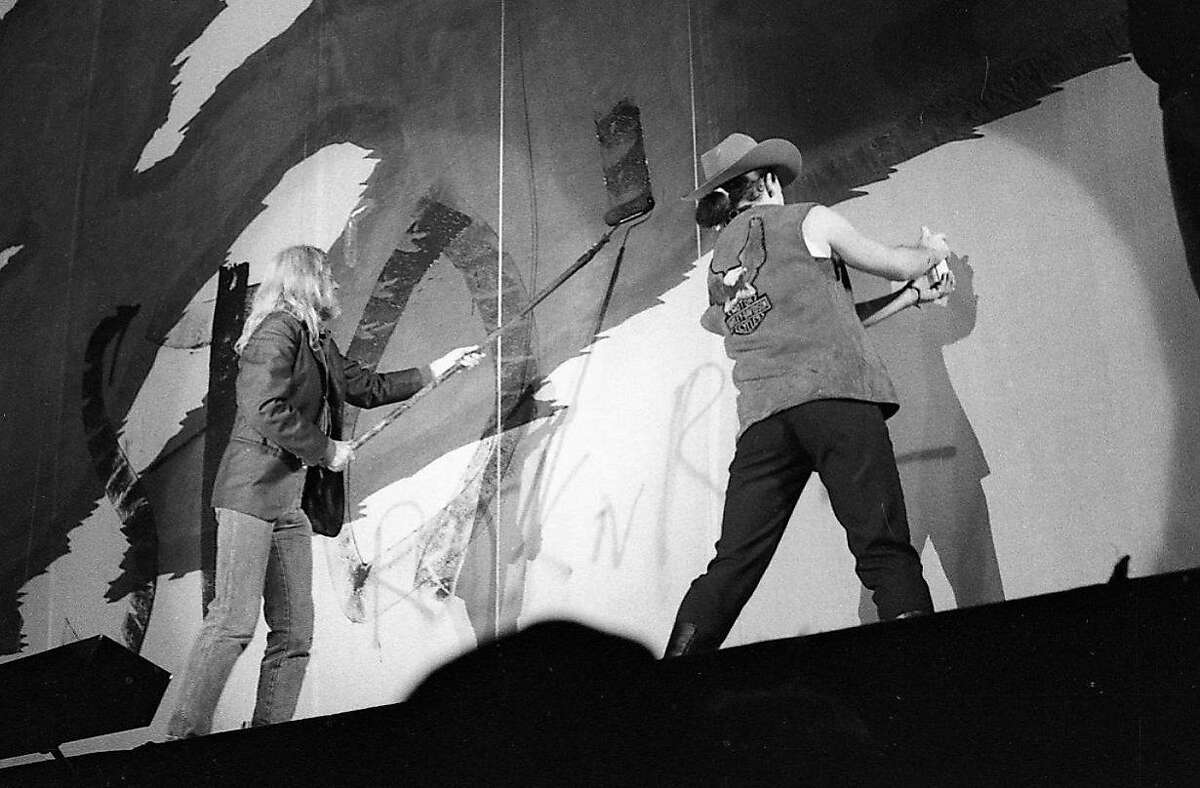U2 singer Bono and Armond Vaillancourt paint on stage at a concert in Oakland Coliseum. Nov. 14, 1987.