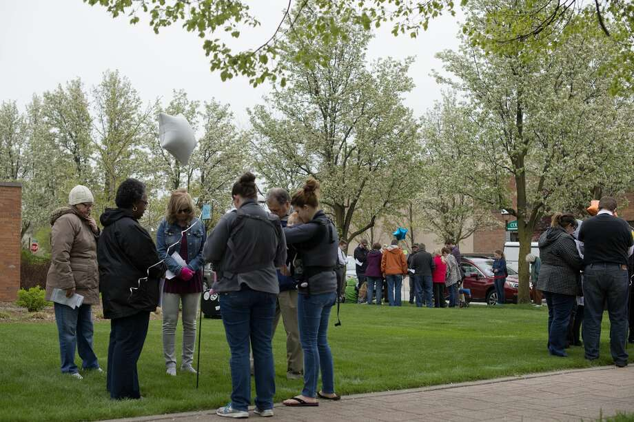 Members of the community gather on the front lawn of First United Methodist Church to participate in the National Day of Prayer. The National Day of Prayer is an annual observance held on the first Thursday of May. It was created in 1952 by a joint resolution of the United States Congress, and signed into law by President Harry S. Truman. For one hour participants moved to seven different stations to pray for the government, military, business, education, church, family or the media. Photo: Brittney Lohmiller/Midland Daily News/Brittney Lohmiller