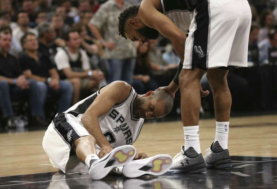 Spurs' Patty Mills looks over Tony Parker after Parker injured his left leg in the second half of Game 2 of the Western Conference semifinals at the AT&T Center against the Houston Rockets in San Antonio on May 3, 2017. Photo: Jerry Lara /San Antonio Express-News / '2017 San Antonio Express-News