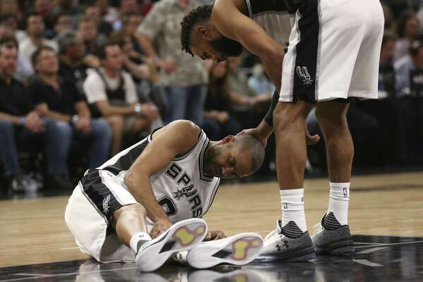 Spurs' Patty Mills looks over Tony Parker after Parker injured his left leg in the second half of Game 2 of the Western Conference semifinals at the AT&T Center against the Houston Rockets in San Antonio on May 3, 2017.