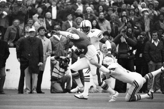 11/27/1976 - Rice Owls defenders try to slowdown Houston Cougars running back Alois Blackwell (32) at Rice Stadium.