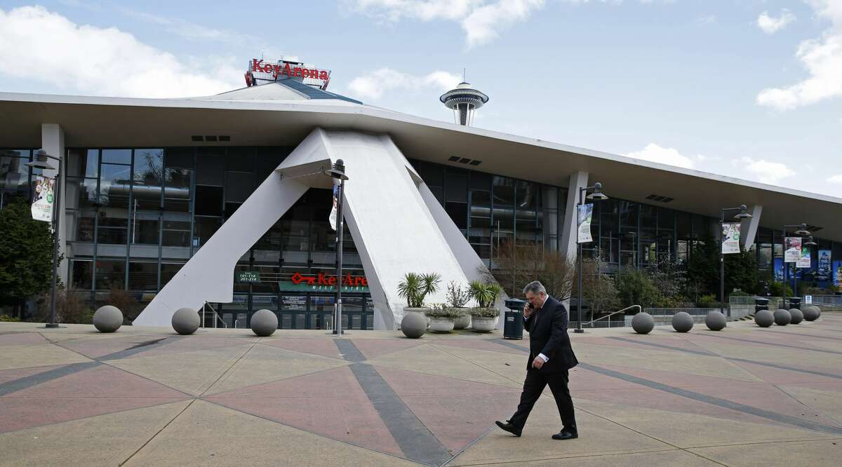 In this March 16, 2017 photo, Tim Leiweke, head of the Oak View Group, talks on his phone as he walks in front of KeyArena in Seattle. Keep clicking to see photos of KeyArena through the years. (AP Photo/Ted S. Warren)