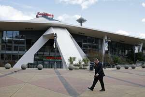 In this March 16, 2017 photo, Tim Leiweke, head of the Oak View Group, talks on his phone as he walks in front of KeyArena in Seattle. Leiweke is expected to submit a proposal for a renovation of KeyArena, which formerly was home to the NBA's Seattle SuperSonics. Seattle is in the midst of an arena showdown with three groups putting forth proposals around two sites to build the possible future home for teams from in the NBA basketball and NHL hockey leagues. (AP Photo/Ted S. Warren)