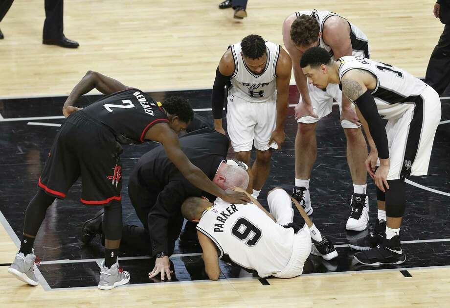 Houston Rockets' Patrick Beverley (2) checks on the Spurs' Tony Parker (9) along with Parker's teammates (from left) Patty Mills, Pau Gasol and Danny Green and Spurs' athletic trainer Will Sevening during the second half of Game 2 at the AT&T Center on May 3, 2017, in San Antonio. The Spurs announced on Thursday that Parker has a ruptured quadriceps tendon in his left leg. Photo: Kin Man Hui /Associated Press / '2017 San Antonio Express-News