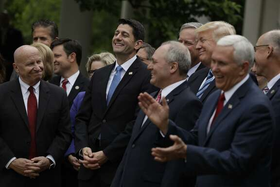 Republican politicians, including House Speaker Paul Ryan (second from left), President Trump (second row, second from right) and Vice President Mike Pence (right), celebrate their legislation's passage in the White House Rose Garden.