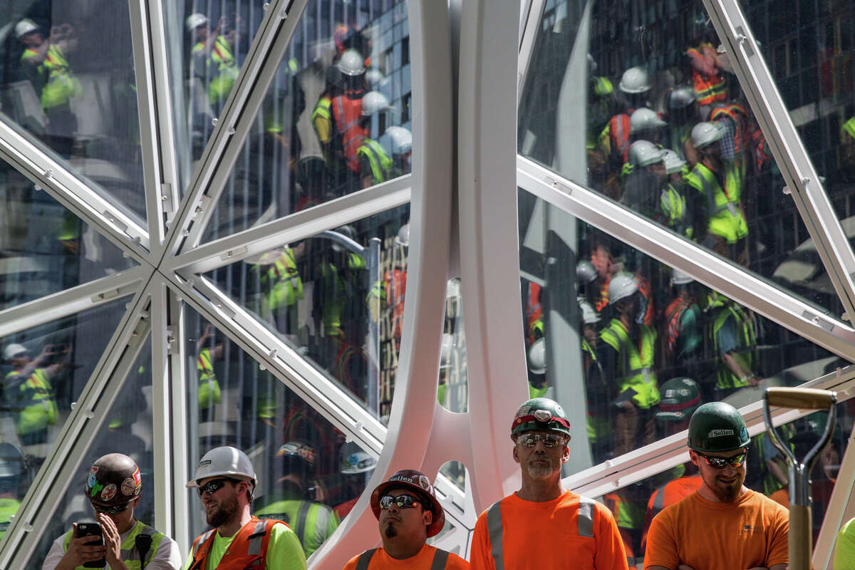 Construction workers line the walls of Amazon's biospheres during a ceremony celebrating the Spheres' first plant, on Thursday, May 4, 2017.