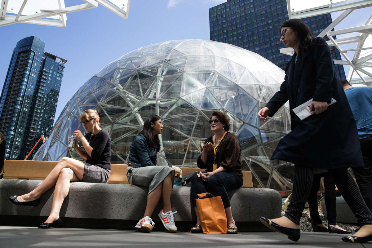 """People enjoy a rare sunny lunch hour outside Amazon's biospheres, """"The Spheres"""" on Thursday, May 4, 2017."""