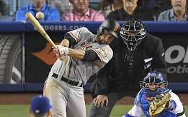 San Francisco Giants' Brandon Belt, left, hits an RBI single as Los Angeles Dodgers catcher Yasmani Grandal, right, and home plate umpire Hunter Wendelstedt watch during the 11th inning of a baseball game, Wednesday, May 3, 2017, in Los Angeles. (AP Photo/Mark J. Terrill)
