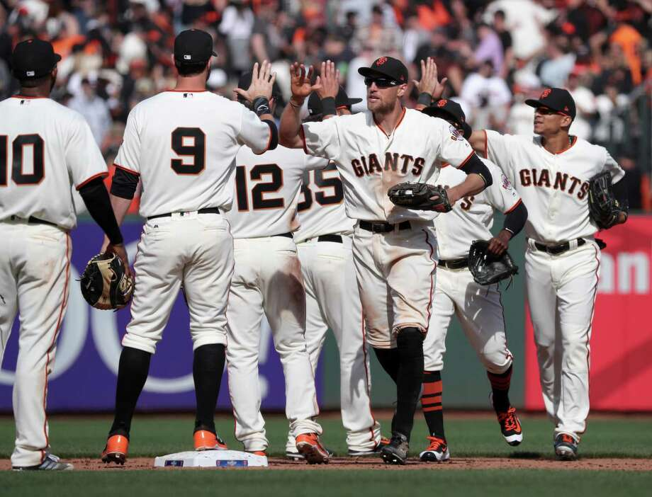 Hunter Pence, (center) joins the team in celebration as the San Francisco Giants beat the Arizona Diamondbacks 4-1 in their home opener at AT&T Park in San Francisco, Calif. on Mon. April 10, 2017. Photo: Michael Macor / The Chronicle / ONLINE_YES