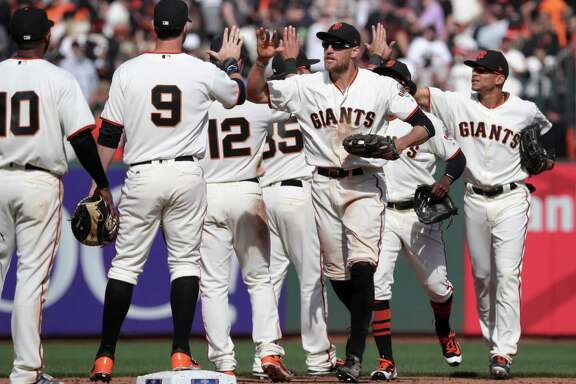 Hunter Pence, (center) joins the team in celebration as the San Francisco Giants beat the Arizona Diamondbacks 4-1 in their home opener at AT&T Park in San Francisco, Calif. on Mon. April 10, 2017.