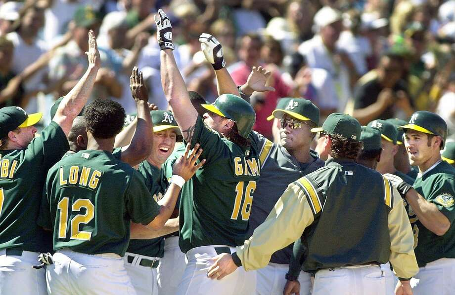 Oakland Athletics' Jason Giambi (16) is surrounded by teammates following his game-winning two-run home run in the bottom of the ninth inning against the New York Yankees, Sunday, Aug. 12, 2001, in Oakland, Calif. The 4-2 win gave the A's a sweep of the three-game series. (AP Photo/San Francisco Chronicle, Lacy Atkins) Photo: LACY ATKINS / Lacy Atkins / The Chronicle 2001 / SAN FRANCISCO CHRONICLE