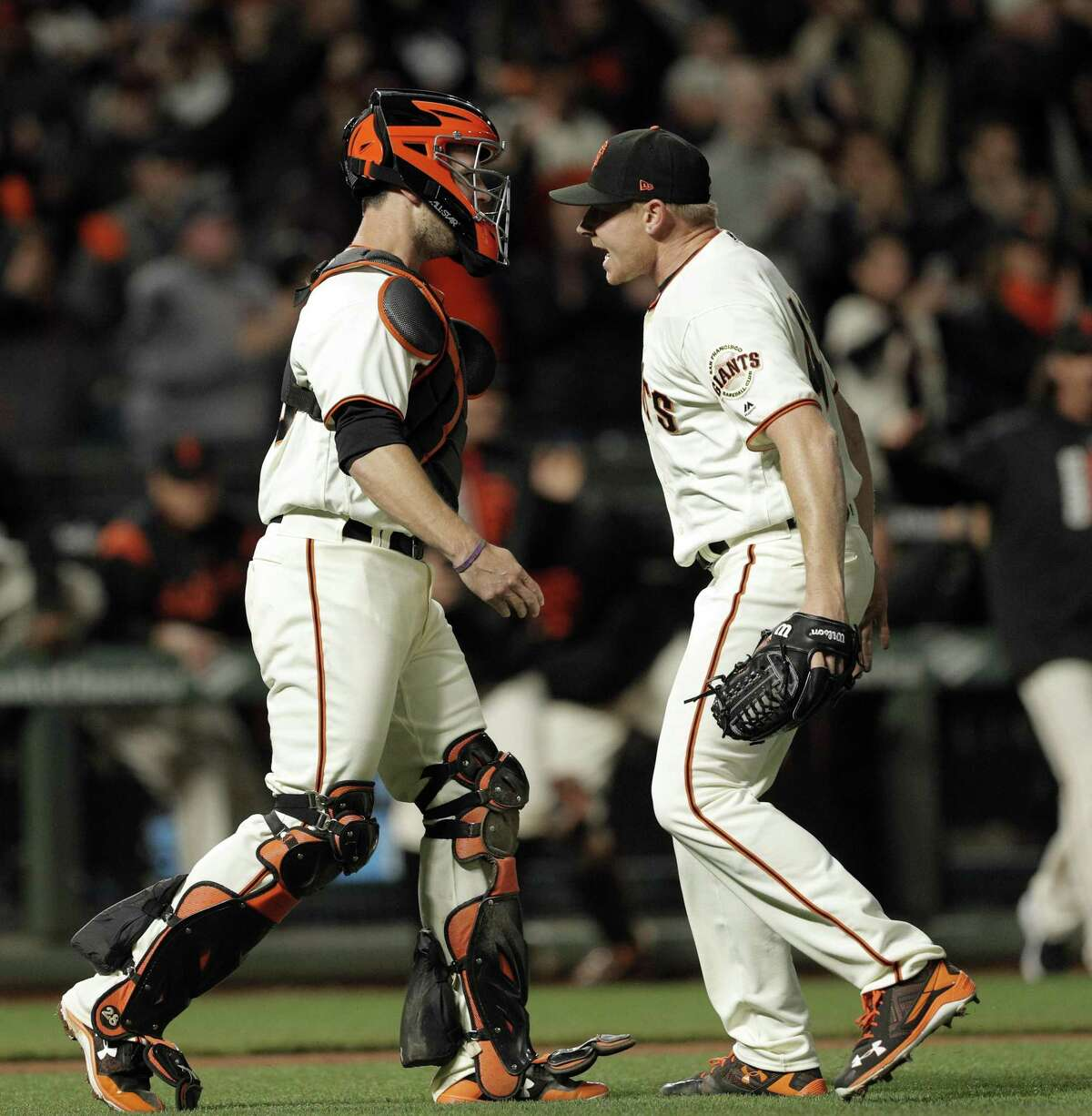 Mark Melancon (41) celebrates with Buster Posey (28) after Posey got the last out on an attempted steal as the San Francisco Giants played the Los Angeles Dodgers at AT&T Park in San Francisco, Calif., on Monday, April 24, 2017.