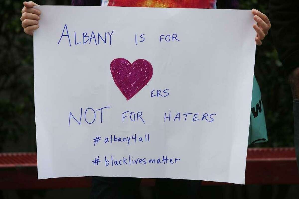 A woman holds up a sign in the crowd at a gathering in response the cyber bullying at Albany High School on Sunday, March 26, 2017, in Albany, Calif.