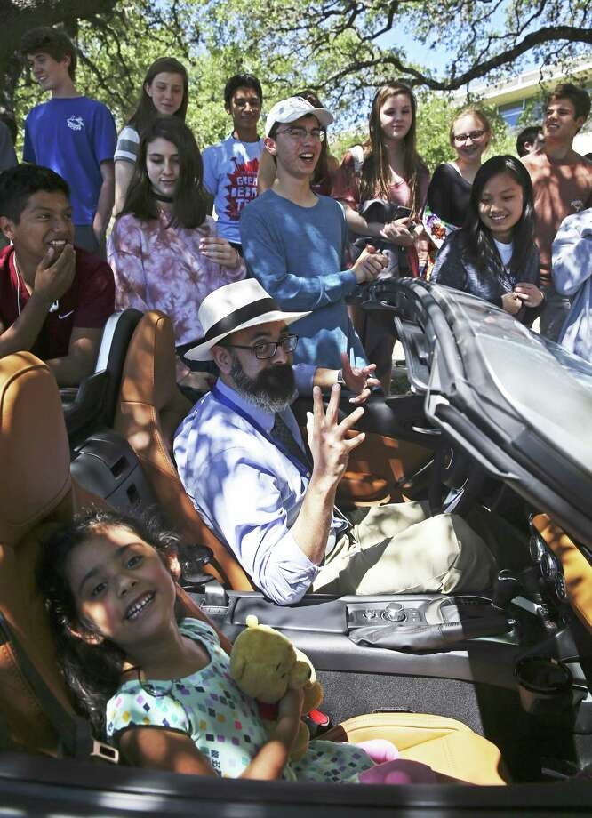 Students gather around a Fiat convertible as Alamo Heights Teacher of the Year, Eric Cruz, accepts the reward of a new car to drive for each different season of the coming year from the Principle Auto Group on May 4, 2017 at the High School. In the car also is daughter Catalina. Photo: Tom Reel, Staff / San Antonio Express-News / 2017 SAN ANTONIO EXPRESS-NEWS