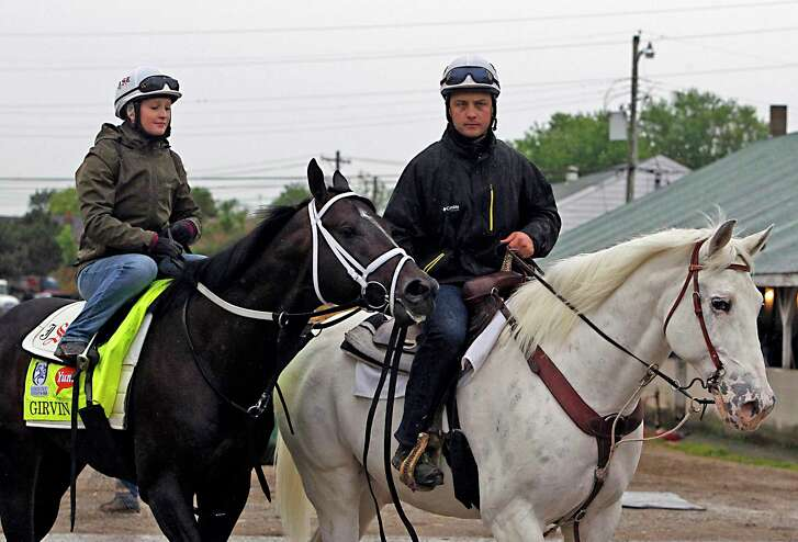Trainer Joe Sharp, right, leads Kentucky Derby entrant Girvin, ridden by wife Rosie Napravnik, back to Barn 33 after a morning gallop at Churchill Downs.