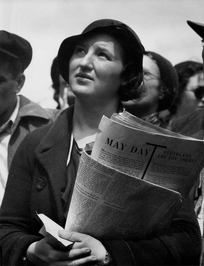 """Right: Lange's photo from 1934 titled """"May Day Listener at Rally."""" Photo: Oakland Museum Of California, Gift Of Paul S. Taylor, Collecti"""