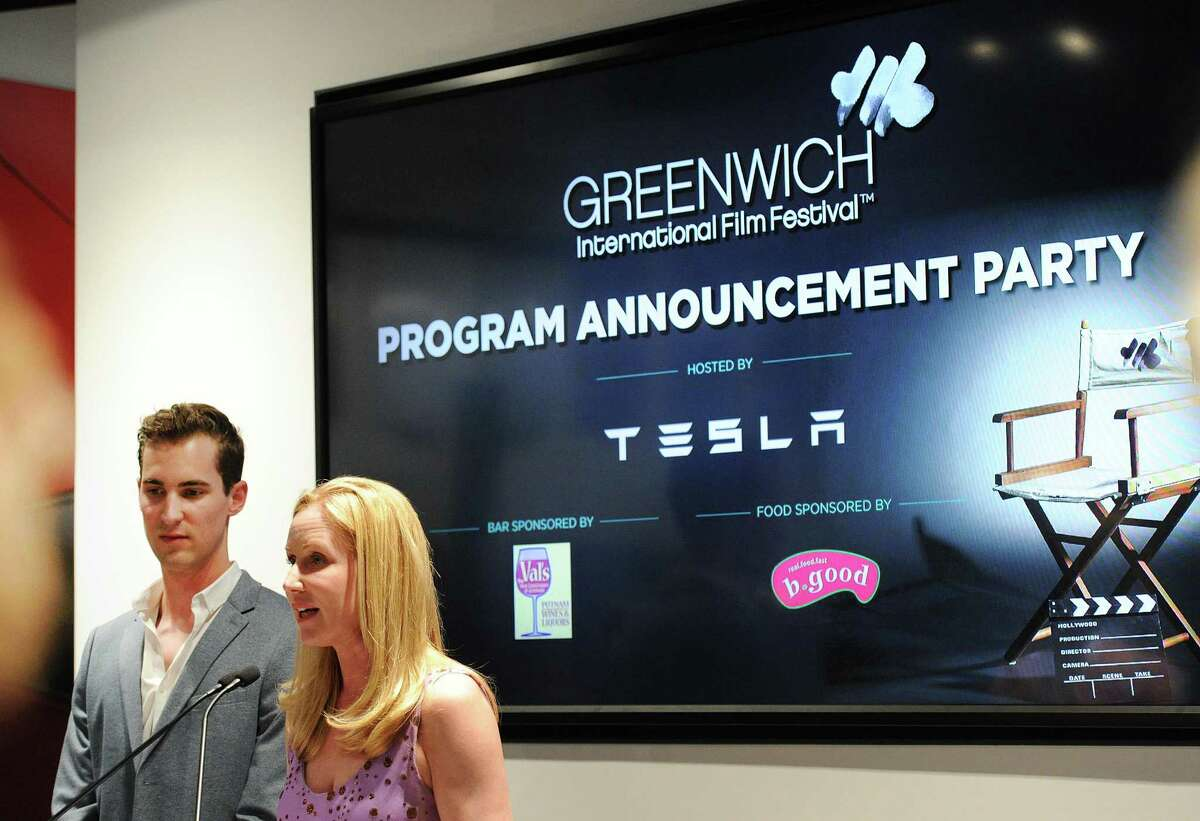 Colleen deVeer, right, one of the founders of the Greenwich International Film Festival, speaks during the film festival's announcement event at the Tesla Showroom in Greenwich on Thursday. At left is Sam Kleiner, a film-maker and GIFF team member.