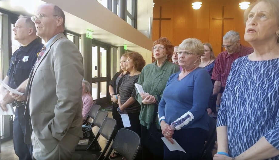 """HPD Officer Mike Liesmann, Fred Kessler and Kingwood community members sing """"God Bless America"""" during the National Day of Prayer event at Kingwood United Methodist Church April 4. Photo: Melanie Feuk"""