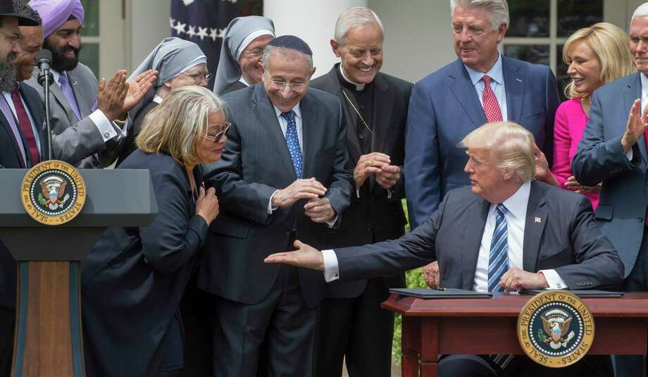President Donald Trump reaches out to Alveda King, a niece of Martin Luther King Jr., during a National Day of Prayer event at the White House on Thursday. Trump signed an executive order directing the IRS to avoid cracking down on political activity by religious groups.  Photo: STEPHEN CROWLEY, STF / NYTNS