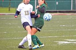 Father McGivney's Marta Korte, left, and Metro-East Lutheran's Reagan Guerra battle for the ball during Thursday's game.