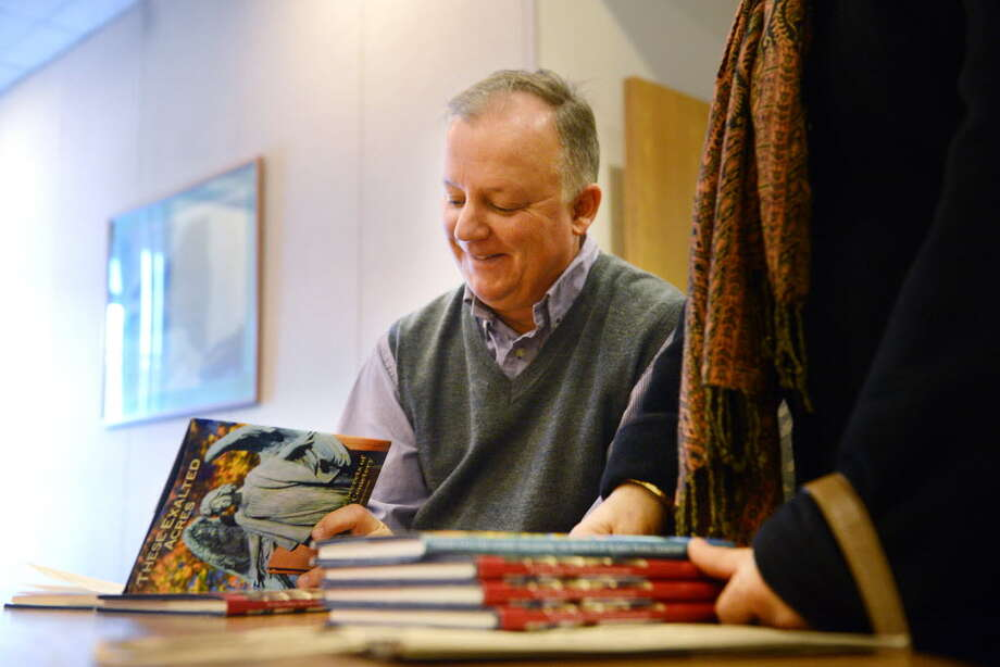 """Paul Grondahl signs copies of """"These Exalted Acres"""" and """"The Story of Albany"""" on Dec. 10, 2014, during a book signing at the Times Union in Colonie. (Will Waldron / Times Union)"""