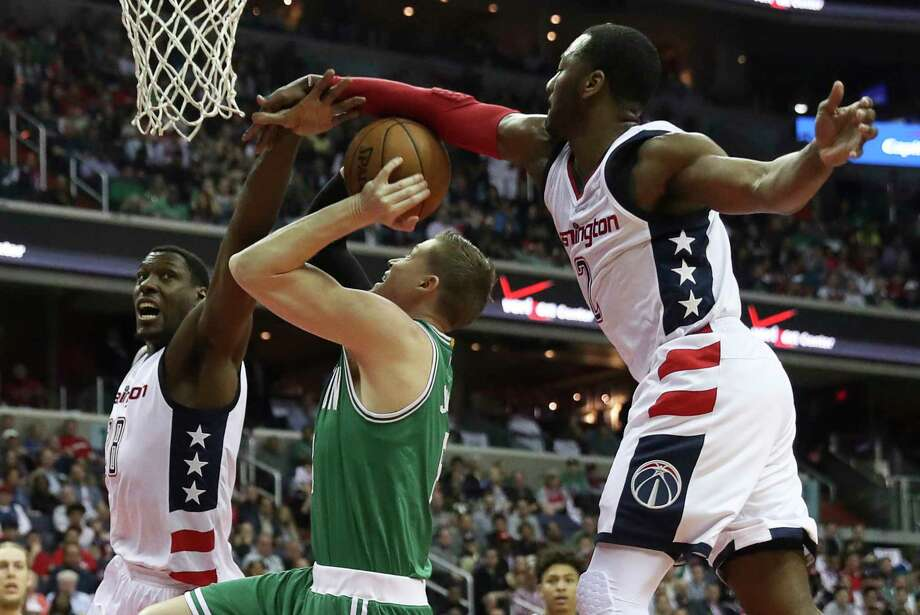 Celtics forward Jonas Jerebko, center, draws a foul as the Wizards' Ian Mahinmi , left, and John Wall defend during the first half.   Photo: Andrew Harnik, STF / Copyright 2017 The Associated Press. All rights reserved.