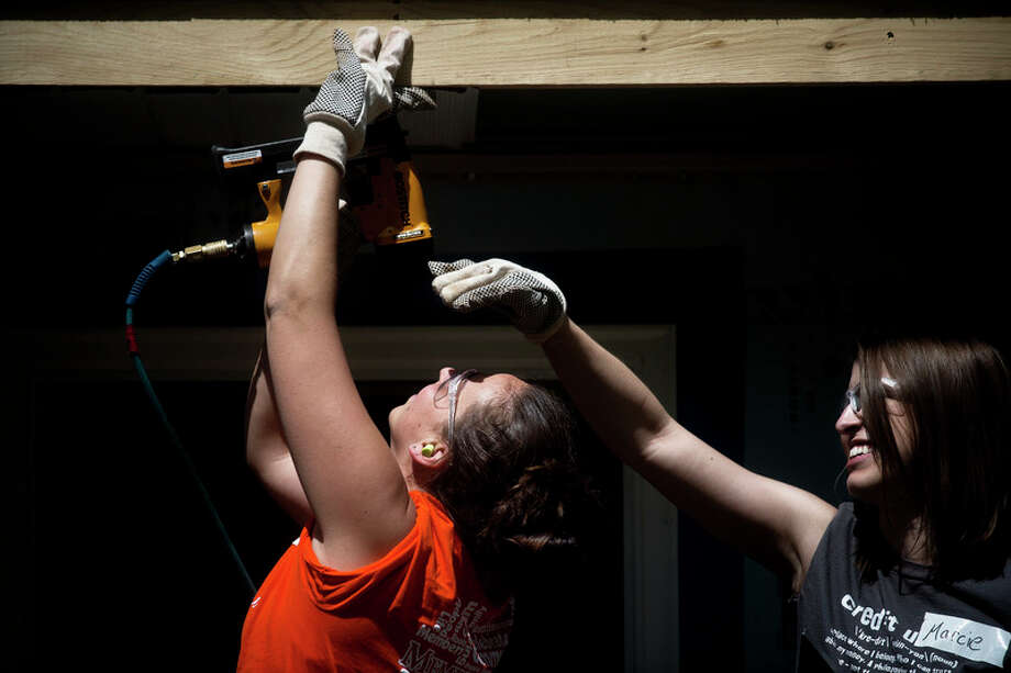 SEAN PROCTOR | sproctor@mdn.net Jayme Manderach, of Kawkawlin, works on constructing the Stillwagon's new house May 12, 2013 as Marcie Long, of Sanford, shades her eyes from the sun. Both Manderach and Long work for Members First Credit Union, and were volunteering as part of Habitat for Humanity's Women Build Week. This year's Women Build Week will start May 8. / (c)Sean Proctor (c) Midland Daily News