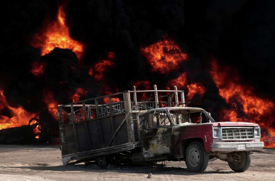 FILE - State policemen take pictures following the explosion of a petrol pipeline caused by fuel theft, in Acatzingo, Puebla State, on March 7, 2017. In Mexico's Puebla state, gunmen using local residents as a human shield opened fire on a Mexican army patrol investigating fuel pipeline thefts, killing two soldiers and wounding a third, the military said Thursday, May 4, 2017. Photo: JOSE CASTANARES/AFP/Getty Images