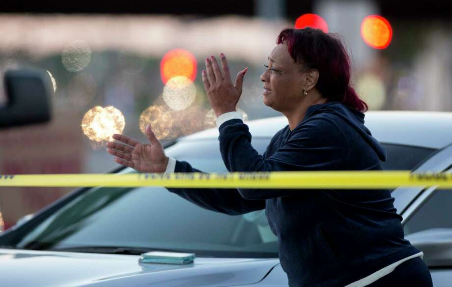 The mother of the man who was fatally stabbed in the neck by three suspects watches as Houston Police officers investigate the scene on the 11600 block of Southwest Freeway ear Wilcrest Friday, May 5, 2017, in Houston. Photo: Godofredo A. Vasquez, Houston Chronicle / Godofredo A. Vasquez